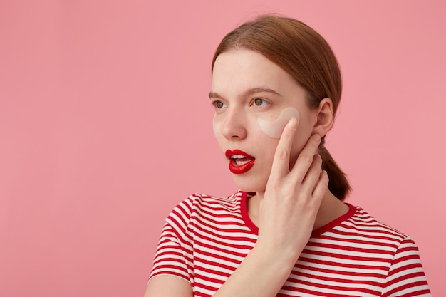 Zbliżenie na myślącą młodą rudowłosą dziewczynę z czerwonymi ustami i łatami pod oczami, ubrana w czerwoną koszulkę w paski, odwraca wzrok, dotyka policzka, wstaje.