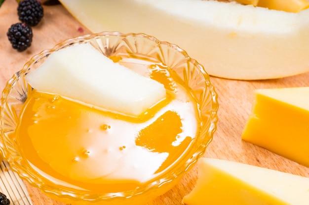 Zbliżenie na naczynie z przetworami owocowymi do maczania, jako część tablicy z owocami i serami dla smakoszy