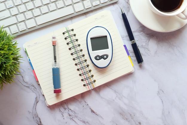 Zbliżenie na narzędzia do pomiaru cukrzycy, notatnik, klawiatura na stole