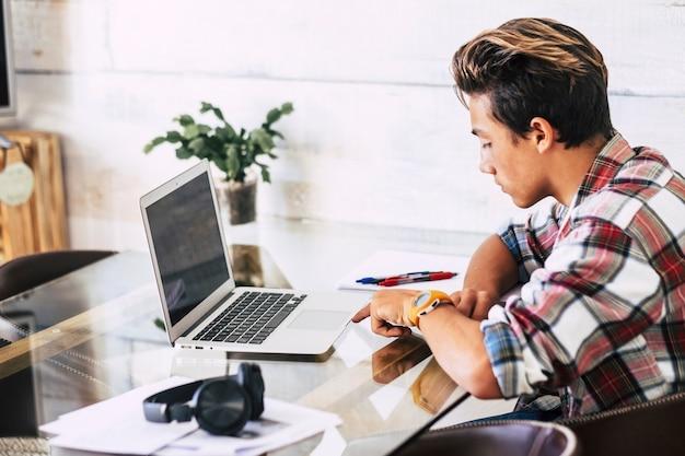 Zbliżenie na nastolatka ze słuchawkami, patrząc na laptopa, odrabiania lekcji w ciszy - kryty fokus facet - kaukaski chłopiec koncentruje się na swojej pracy
