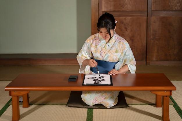 Zbliżenie na nauczyciela wykonującego japońską kaligrafię, zwaną shodo