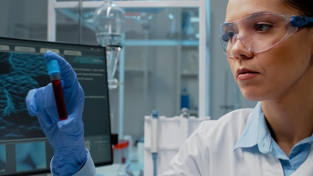 Zbliżenie na naukowca analizującego laboratorium vacutainer z płynem