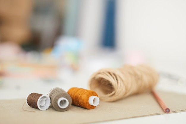 Zbliżenie na nici leżące na stole i gotowe do szycia