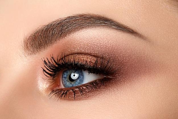 Zbliżenie na niebieskie oko kobiety z pięknym brązowym z czerwonymi i pomarańczowymi odcieniami makijażu smokey eyes. makijaż nowoczesnej mody.