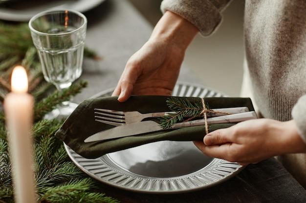 Zbliżenie na nierozpoznawalną kobietę nakrywającą stół jadalny ozdobiony na boże narodzenie gałązkami jodły...