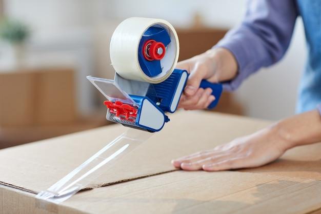 Zbliżenie na nierozpoznawalną młodą kobietę za pomocą dozownika taśmy do pakowania pudełek podczas wyprowadzki lub przenoszenia