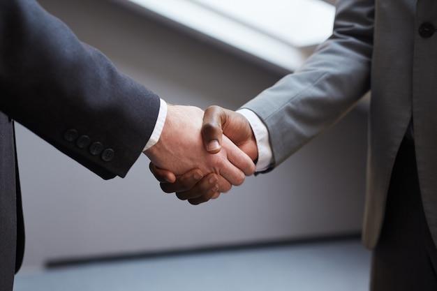 Zbliżenie na nierozpoznawalnego biznesmena odnoszącego sukcesy, ściskającego dłoń z afroamerykańskim partnerem po zawarciu umowy, minimalne tło w odcieniach szarości, miejsce na kopię