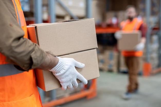 Zbliżenie na nierozpoznawalnego poruszacza w rękawiczkach i pomarańczowej kamizelce niosącego dwa pudełka podczas pracy w magazynie