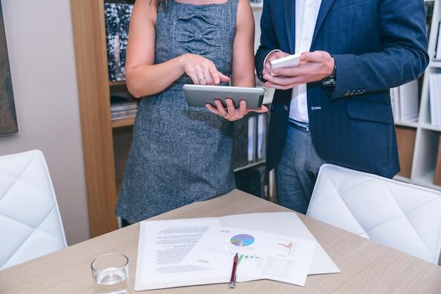 Zbliżenie na nierozpoznawalnych kolegów szukających smartfona i elektronicznego tabletu podczas spotkania biznesowego