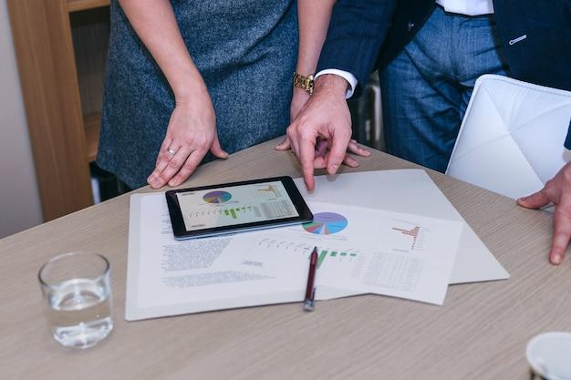 Zbliżenie na nierozpoznawalnych kolegów z elektronicznym tabletem i dokumentami podczas spotkania biznesowego