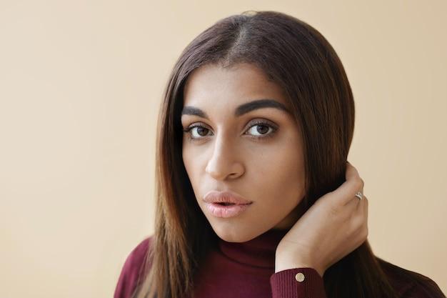 Zbliżenie na niesamowitą, młodą, ciemnoskórą kobietę z długimi brunetkami i czystą, idealną skórę pozującą, patrząc z lekko rozchylonymi ustami, dopasowując fryzurę. strzał poziomy