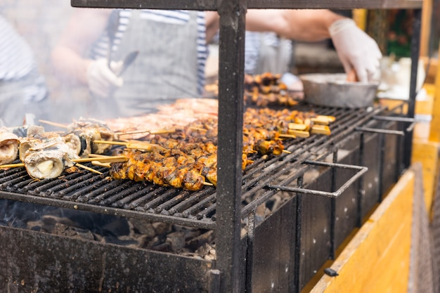 Zbliżenie na niezidentyfikowanych ludzi gotujących mięsne szaszłyki nad paleniem gorącego grilla