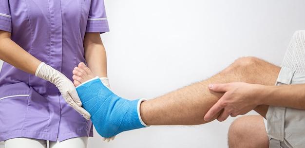 Zbliżenie na nogę mężczyzny w gipsie i niebieską szynę po bandażowaniu w szpitalu.