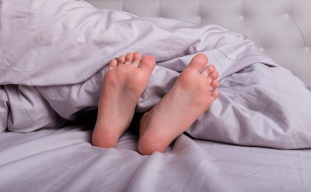 Zbliżenie na nogi dziecka na łóżeczku pod kocem