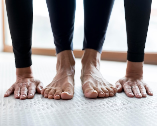 Zbliżenie na nogi i ręce wykonujące ćwiczenia rozciągające