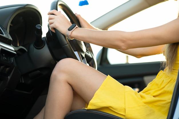 Zbliżenie na nogi młoda kobieta kierowca w żółtej letniej sukience siedzi za kierownicą jazdy samochodem.