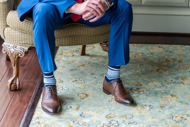 Zbliżenie na nogi pana młodego, siedząc na krześle i czekając na ceremonię