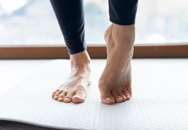 Zbliżenie na nogi wykonujące ćwiczenia rozciągające przed treningiem