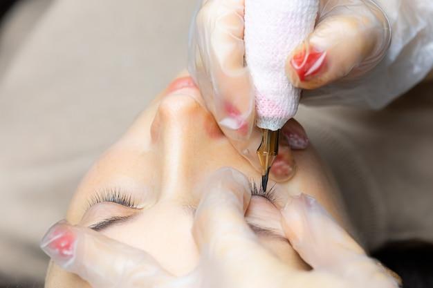 Zbliżenie na nos maszynki do tatuażu, za pomocą której wykonywany jest tatuaż powiek