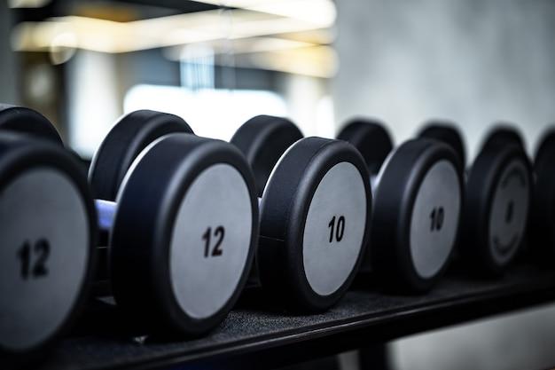Zbliżenie na nowe hantle na stojaku w siłowni