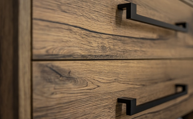 Zbliżenie na nowoczesne meble z ciemnego drewna z czarnymi uchwytami.