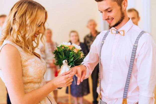 Zbliżenie na nowożeńców, którzy stoją na uroczystej ceremonii i wymieniają obrączki, a za nimi są krewni