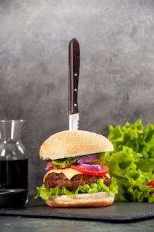 Zbliżenie na nóż w pysznej kanapce z mięsem i zielonym pieprzem na czarnej tacy z sosem pomidorowym z łodygą na szarej powierzchni