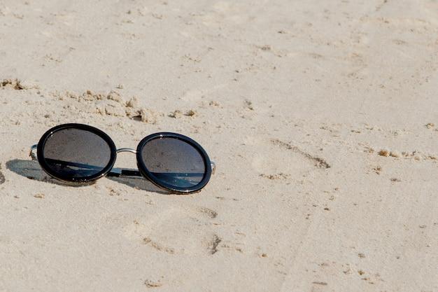 Zbliżenie na okrągłe okulary przeciwsłoneczne na piasku na plaży