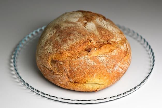 Zbliżenie na okrągły chleb świeżo upieczony chleb na zakwasie ze złotą skórką