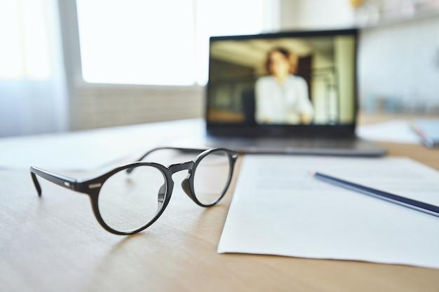 Zbliżenie na okulary na ekranie laptopa stołowego z nauczycielką komunikującą się za pośrednictwem czatu wideo