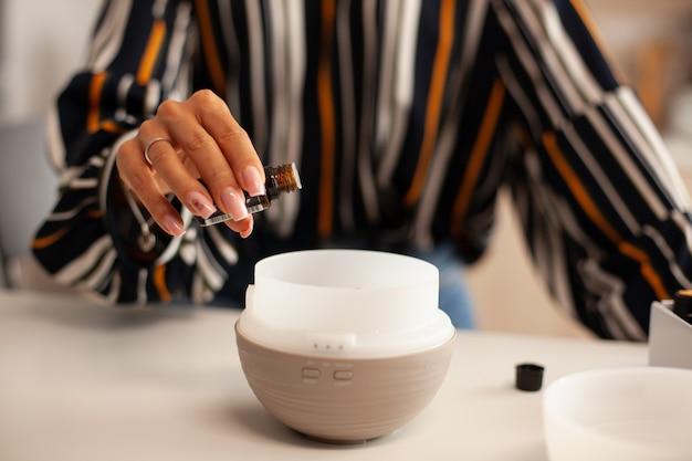 Zbliżenie na olej wlewający się do dyfuzora z kobiecej ręki
