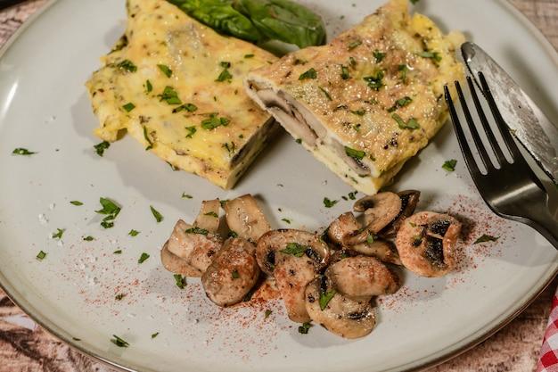 Zbliżenie na omlet z grzybami pokrojony na pół i podany na talerzu z kilkoma smażonymi grzybami