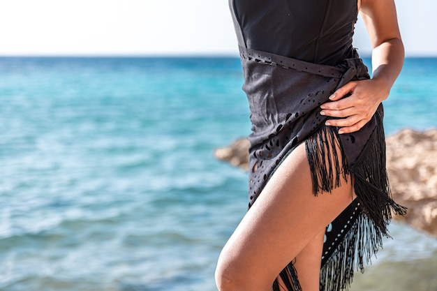 Zbliżenie na opalone nogi dziewczyny w pobliżu morza.