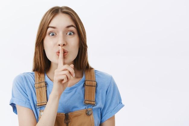 Zbliżenie na optymistyczną, uroczą dziewczynę, która ucisza, przyciska palec do ust, trzyma w tajemnicy lub przygotowuje niespodziankę