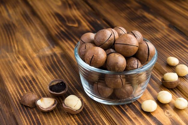 Zbliżenie na orzechy makadamia w szklanej kokardce na drewnianym stole