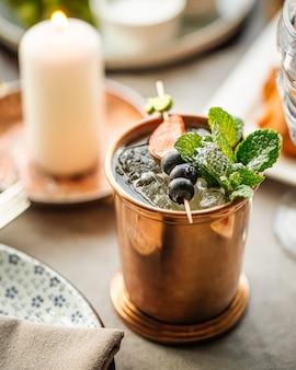 Zbliżenie na orzeźwiający koktajl szampański w kubku miedzi