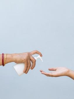 Zbliżenie na osobę nalewającą mydło w płynie do ręki innej osoby