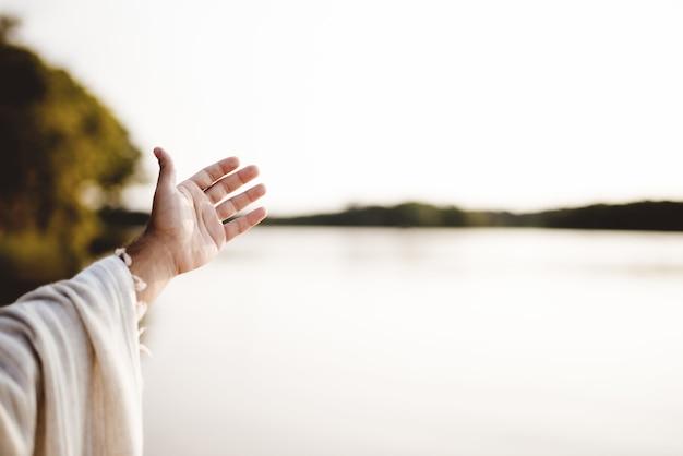 Zbliżenie na osobę ubraną w biblijną szatę z podniesioną ręką