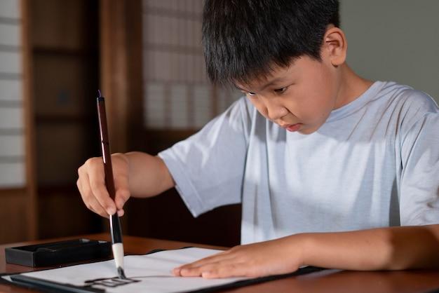 Zbliżenie na osobę wykonującą japońską kaligrafię, zwaną shodo