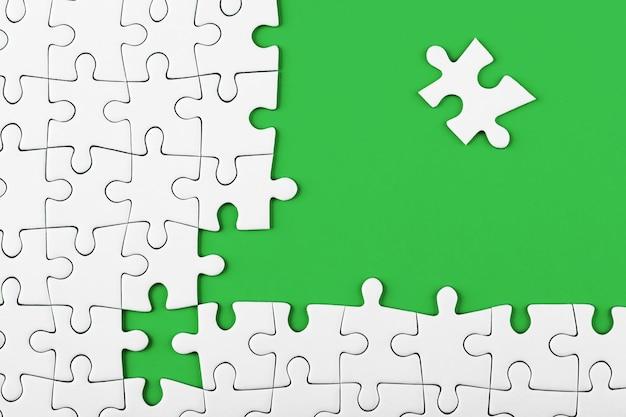 Zbliżenie na ostatni element układanki brakujący na zielono, aby ukończyć misję