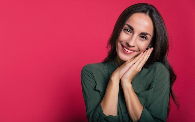 Zbliżenie na oszałamiającą kobietę w sukience khaki, która pozuje z przodu, śmieje się i patrzy w stronę kamery