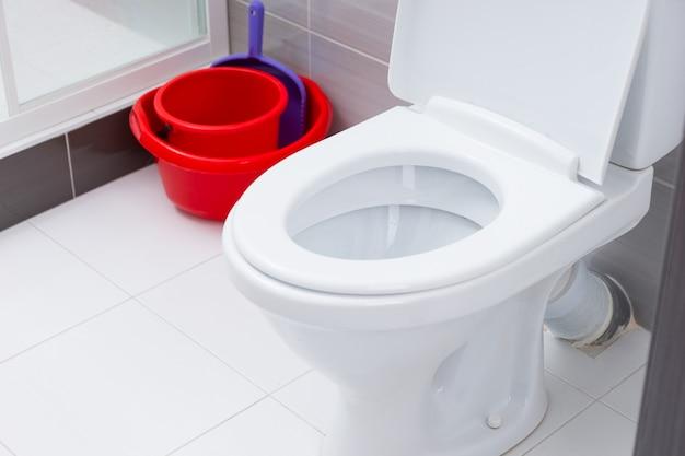Zbliżenie na otwartą toaletę w czystej łazience z biało-szarymi płytkami obok czerwonych wiader do czyszczenia i szufelki