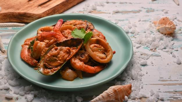 Zbliżenie na owoce morza w proszku curry smażone w proszku na zielonym talerzu ceramicznym na drewnianym stole, tajskie jedzenie