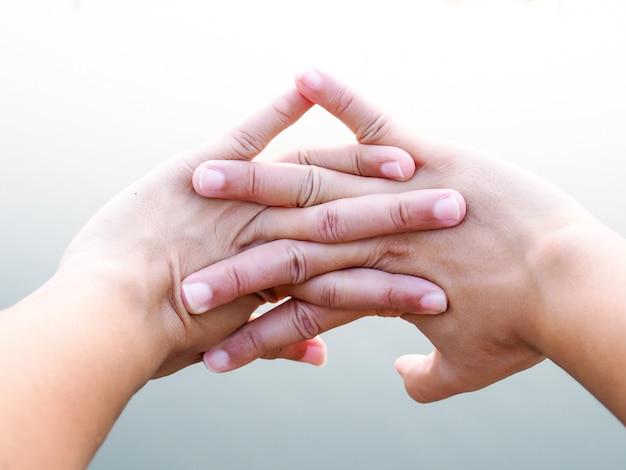 Zbliżenie na palce azjatów z wyciągniętą ręką i ćwiczenia w parku w celu rozluźnienia mięśni łagodzą zmęczenie.