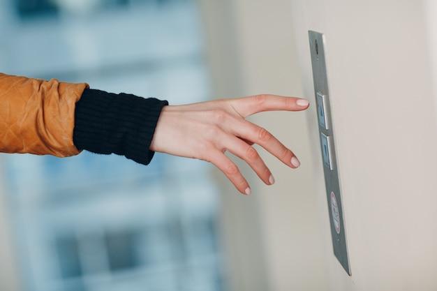 Zbliżenie na palec wskazujący naciskający przycisk windy podczas koncepcji kwarantanny pandemii koronawirusa covid-19