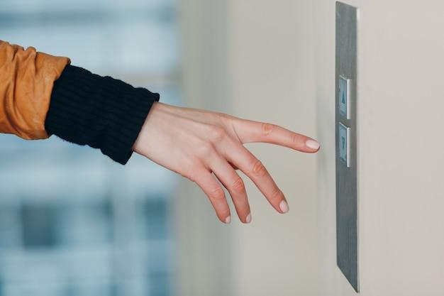 Zbliżenie na palec wskazujący naciskający przycisk windy podczas pandemicznej koncepcji kwarantanny pandemii koronawirusa