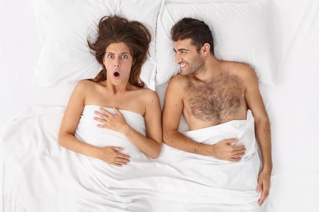 Zbliżenie na parę leżącą w łóżku pod białym kocem