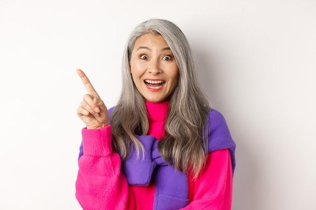 Zbliżenie na piękną azjatycką modelkę wskazując palcem w lewym górnym rogu, uśmiechając się i patrząc na szczęśliwą kamerę, pokazując ofertę promocyjną, białe tło.