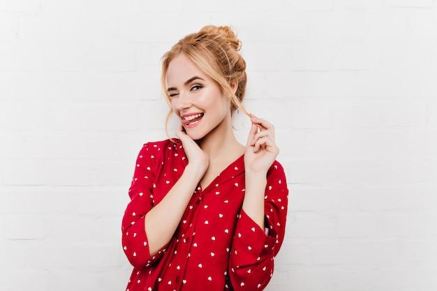 Zbliżenie na piękną kobietę pozującą figlarnie z wystawionym językiem. kryty portret wspaniałej dziewczyny w czerwonym stroju na białym tle na białej ścianie.