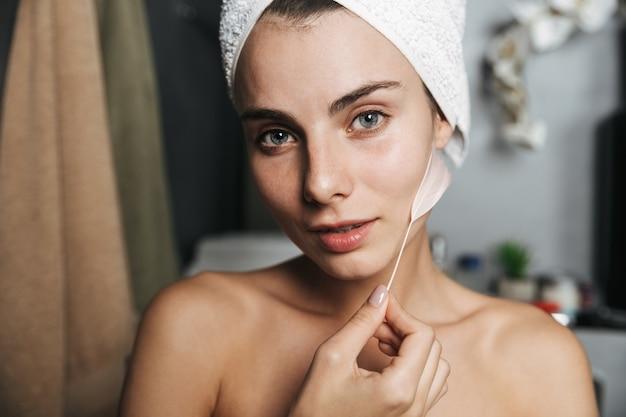 Zbliżenie na piękną, młodą dziewczynę z ręcznikiem owiniętym wokół głowy, dotykając jej skóry piórkiem w łazience